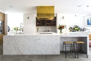 brass finishings and an eye catching range hood contrast with cool carrara marble