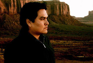 Image of Sherwin Bitsui in closeup, outdoors with the Grand Canyon behind him. The plants in the canyon are green and blooming. Bitsui looks intently toward the distance, out of frame to the camera's right. He wears a black, fleece, pull-over with a zipper and has short, dark hair and dark eyes.