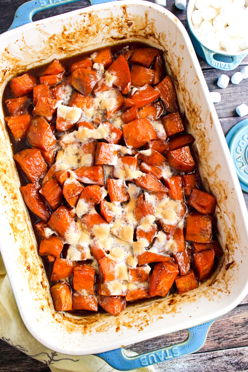 Top view of Candied Sweet Potatoes with Marshmallows in a casserole dish on a rustic wood background.