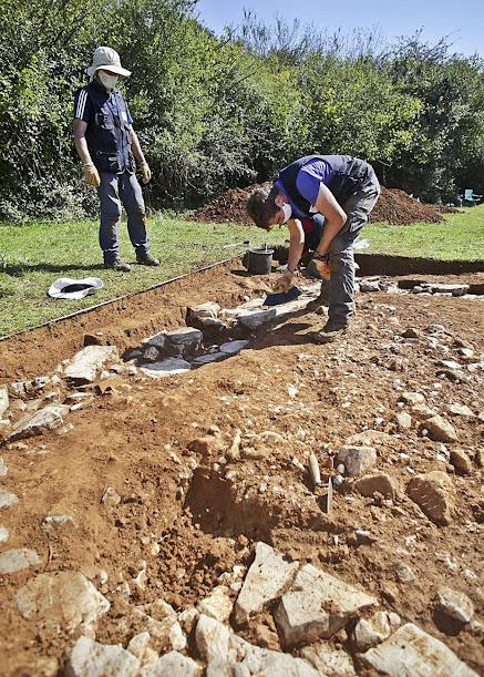 Juan Muñiz, a la izquierda, y Adrián Piñán, ayer, excavando en la construcción descubierta a 25 metros del edificio central de la villa romana. FOTO: IRMA COLLÍN