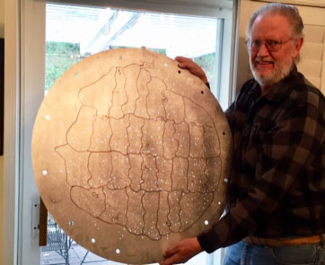 Resident Astronomer George holds one of the disks given away at an AAS meeting  (Source: Palmia Observatory)