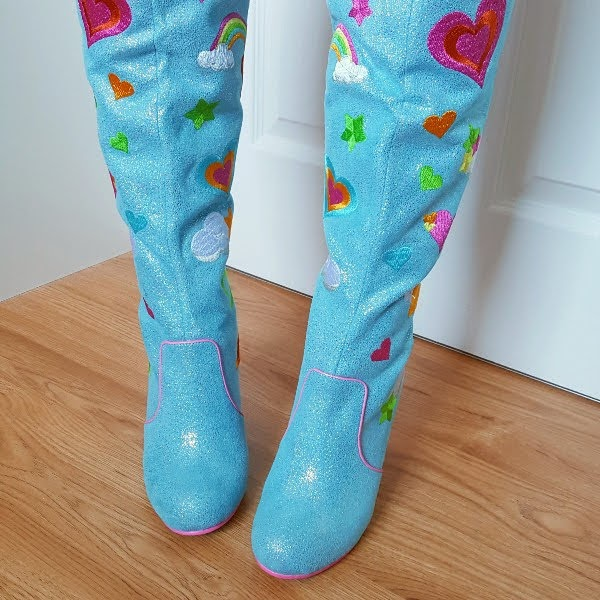 wearing blue boots with embroidered rainbows and clouds and hearts
