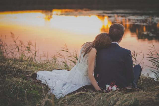 zakochana para nowożeńców siedzi nad brzegiem jeziora o zachodzie słońca
