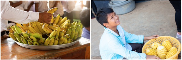 Large tin platter of bananas and a large basket of pineapple being held by a young smiling Cambodian boy