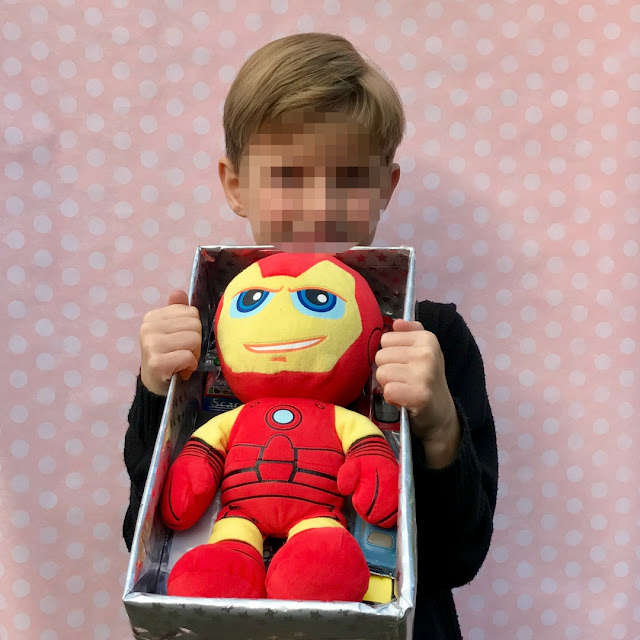 a 7 year old boy (pixelated face) holding a shoebox with a teddy bear inside, pink background with white spots.