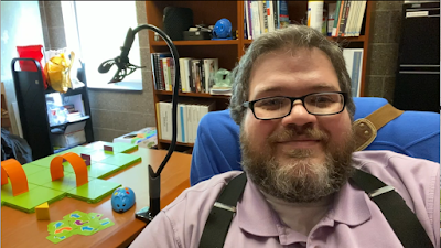 seated man wearing glasses sits and looks straight into the camera. behind him to the right are bookshelves filled with books and to the left is a small maze created from plastic pieces and a small plastic mouse