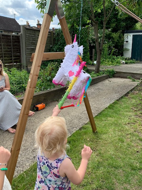 A unicorn pinata being hit by a toddler girl