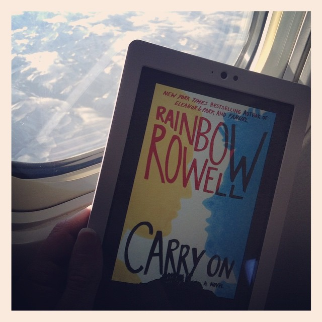 A pale hand holds a white Kobo near an airplane window through which mountains are visible. The Kobo has the cover of Carry On on it, featuring the yellow and blue silhouettes of two boys poised to kiss above a large, visibly ancient estate.