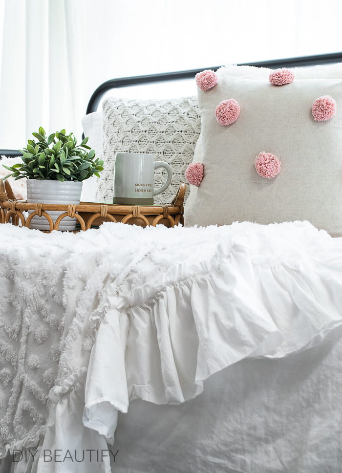 pink pom pom pillow with white chenille throw