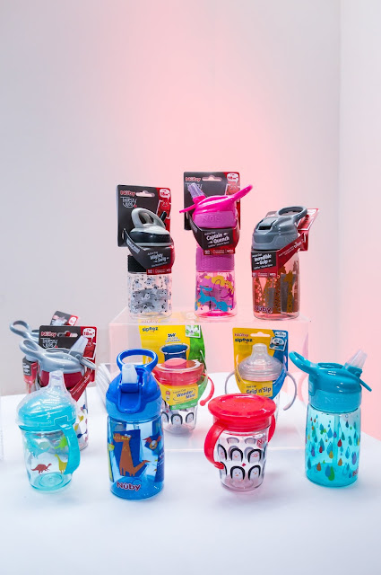 display of colourful patterned kids bottles cups and beakers against white background at nuby big reveal event