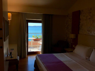 Hotellrom med dobbeltseng. Åpen balkongdør med sjøen i bakgrunnen.