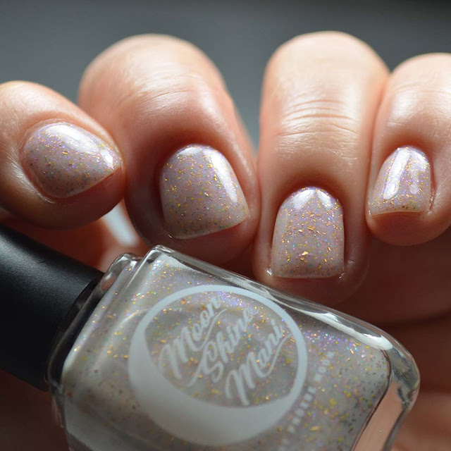 off white nail polish with sparkles and color shifting flakies low light swatch