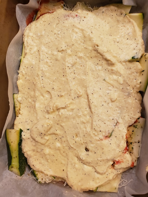 this is whole milk ricotta cheese on top of a pan of layered zucchini to make a lasagna
