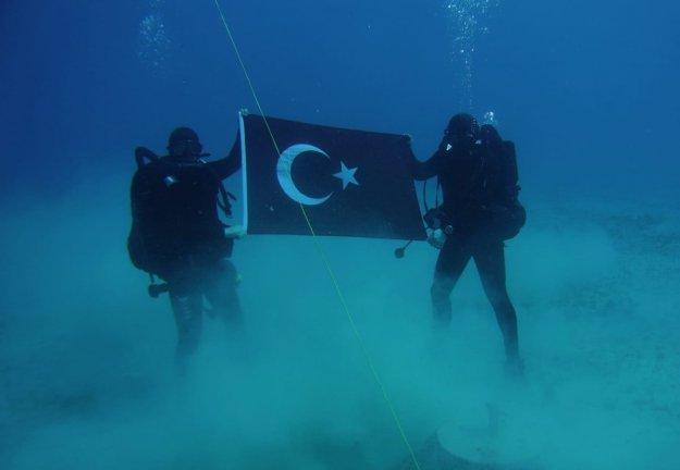 Φωτογραφία με Τούρκους δύτες να κρατούν την τουρκική σημαία στο βυθό της Σούδας