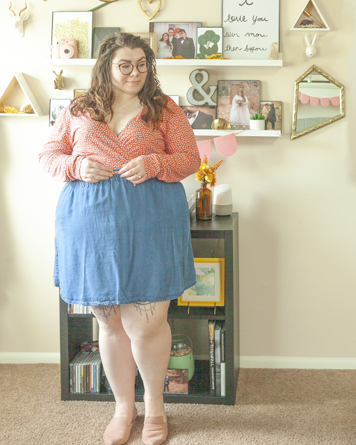An outfit consisting of a pink and orange wrap dress under a blue denim skater skirt and pointed toe pink mules.