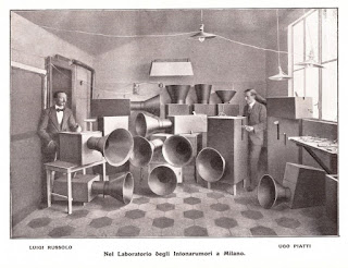 Luigi Russolo (left), his fellow Futurist Ugo Piatti, and a  collection of the intonarumori machines he used for his music