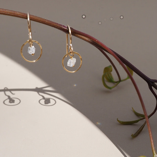 Gold hoop and white gemstone dangly earrings