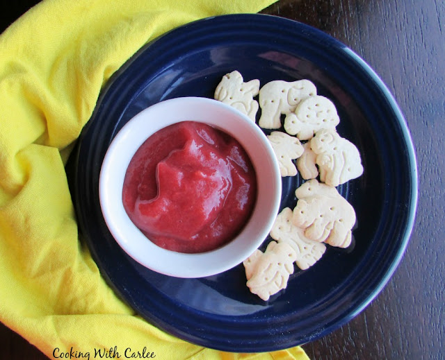 ramekin of pink strawberry rhubarb sauce on plate with animal crackers