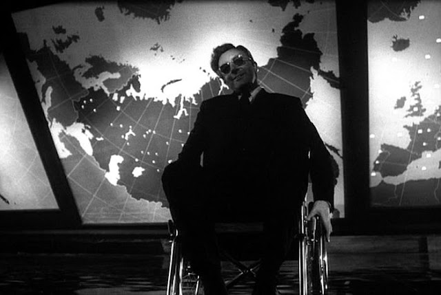 Peter Sellers as Dr. Strangelove in front of a map