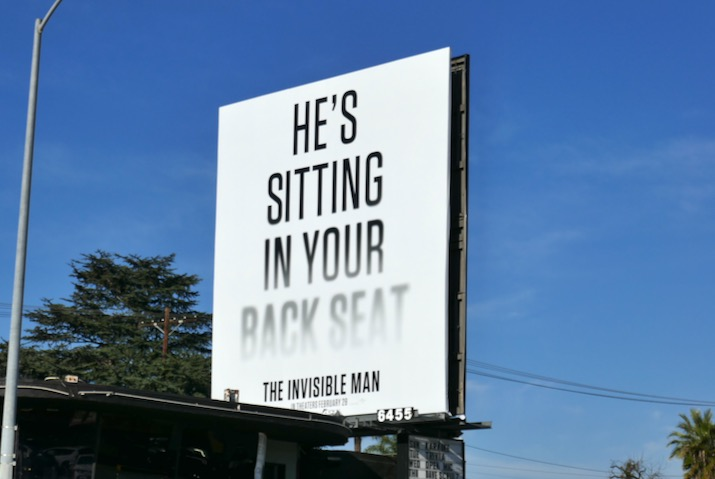 sitting in back seat Invisible Man billboard