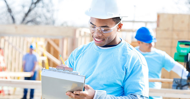 man holding a clipboard in front of a construction site