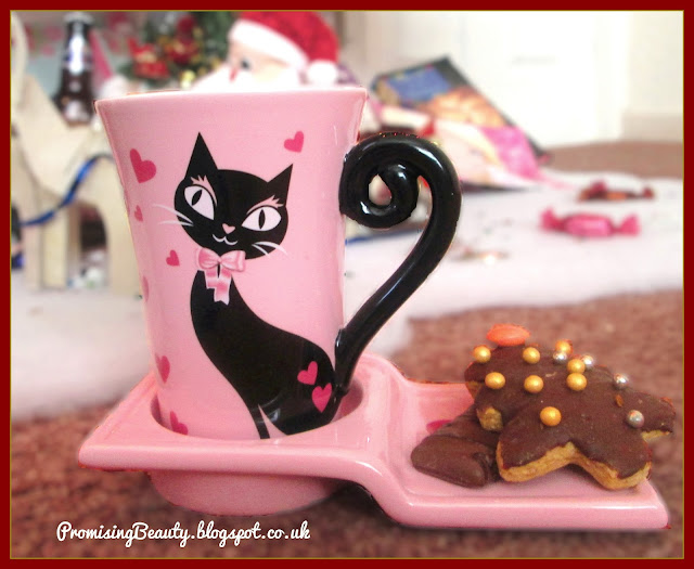 Pink fancy cat mug with bow from avon with home made gingerbread biscuits or cookies dipped in chocolate with golden balls. Sleek cat, cute gift.