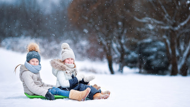 two girls sharing a toboggan as light snow falls