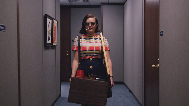 Mad Men's Peggy Olson strides down an office hallway smoking a cigarette, wearing sunglasses, and carrying a file box of her things.