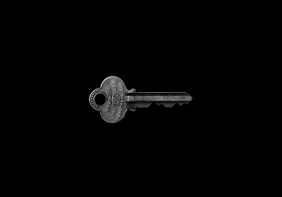 an old silver key on a black background