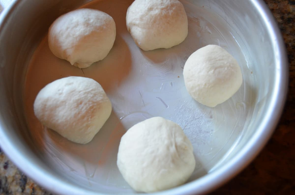 Shaped French Bread Dinner Roll dough in a greased cake pan.