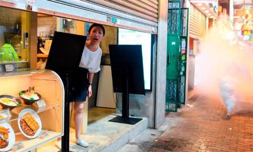 Seorang wanita bereaksi ketika petugas polisi menembakkan peluru gas air mata untuk membubarkan para pemrotes pro-demokrasi di Daerah Sham Shui Po, Hong Kong pada 14 Agustus 2019.