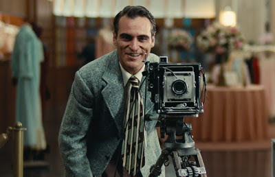 Joaquin Phoenix as Freddie Quell in The Master, smiles and takes a still photograph, standing behind the still camera, directed by Paul Thomas Anderson