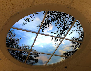 A light box in the ceiling that looks like a blue sky with a crescent moon and tree leaves.