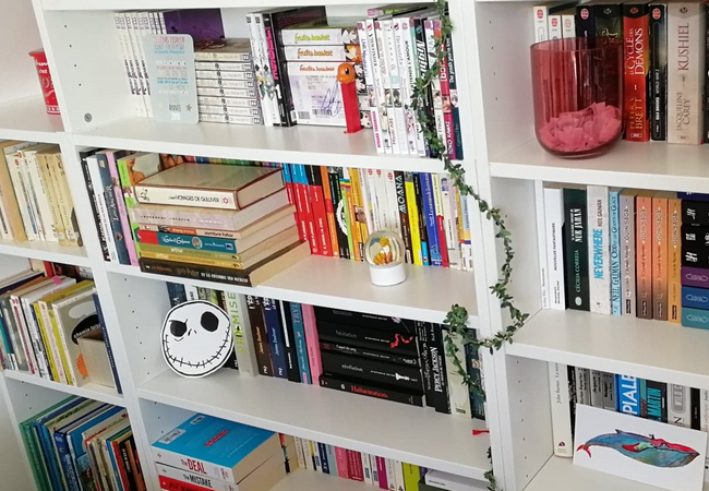 Etagères de ma bibliothèque, avec des livres, des cartes postales et autres goodies.