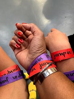 three hands display wristbands of different colours