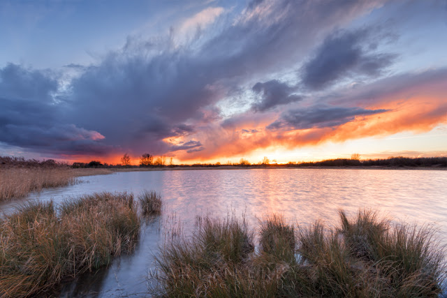 Bright sunset colours fill the clouds and reflect in the lake at Ouse Fen Nature Reserve
