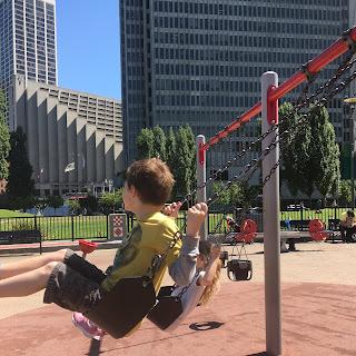 David and Jane swing in the playground
