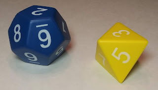 A large blue d12 and a large yellow d8, both made of the same foam used to make stress squeeze toys.