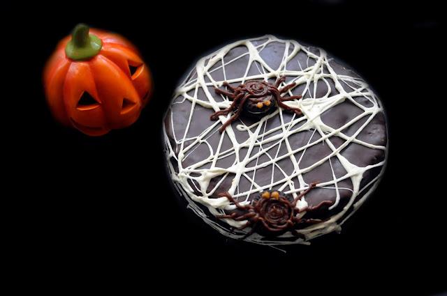 una tarta cubierta de telarañas con dos arañas hechas de oreos