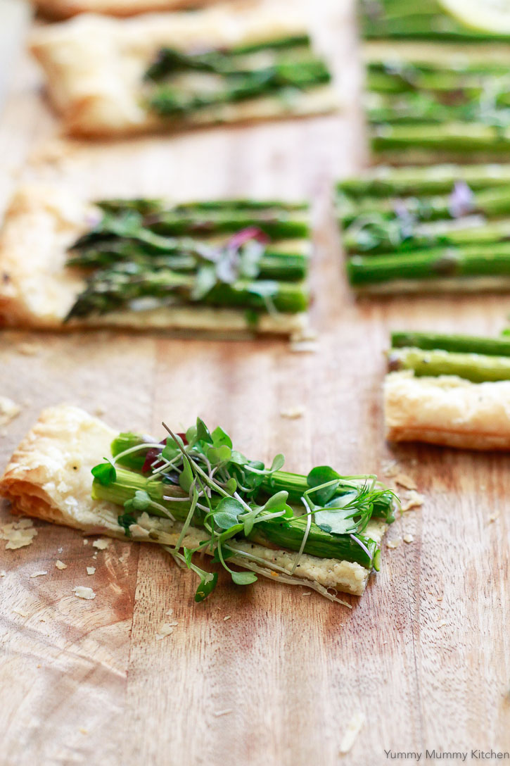 Delicious light puff pastry asparagus tart topped with microgreens and cut into finger-food slices.This easy asparagus tart with goat cheese style spread is so delicious and easy to make vegan or gluten free.