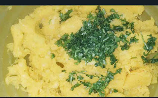 Mixing corriander leaves with potato fillings for bread pakora recipe