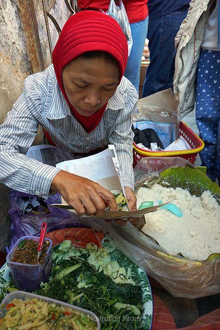 Mbah Tugiyem melayani pembeli nasi urap jagung
