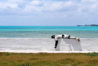 Man laying on wall by the sea.