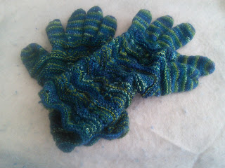 Two Knit Gloves (right hand and left hand mirrored) laying on top of each other, knit in a dark green variegated yarn.