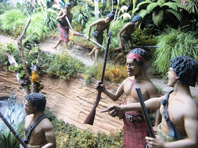 Diorama of 19th-century Maori with muskets on a track in the bush.