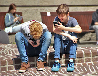 Two young teenagers who present as white boys sit on a brick curb.  One is leaning over looking at his phone, the other is sitting up, looking at his phone.  A person with long hair sits on a bench in the background, also looking at a phone.