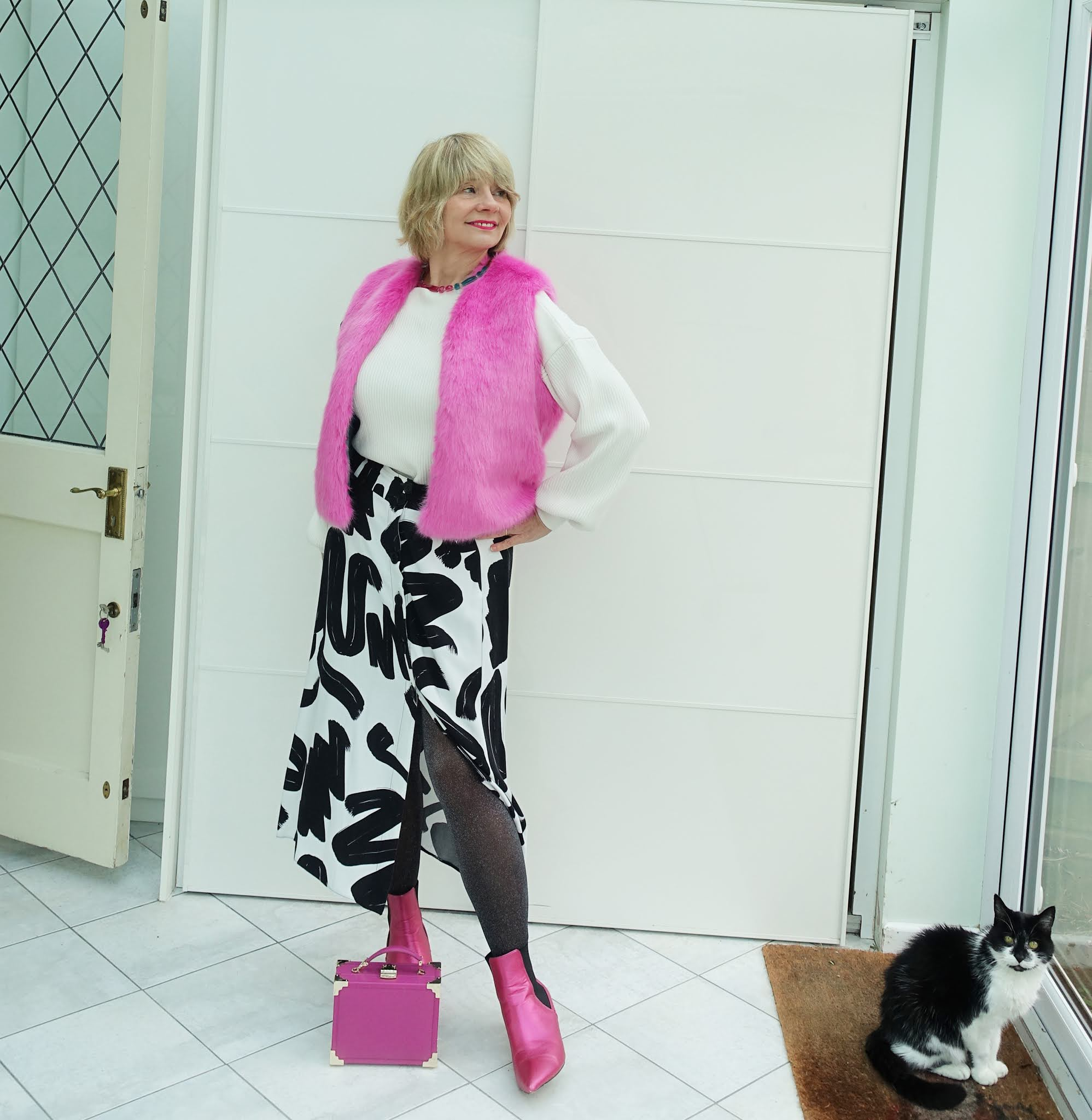 Over 50s style blogger Gail Hanlon in lollipop pink faux fur gilet over black and white