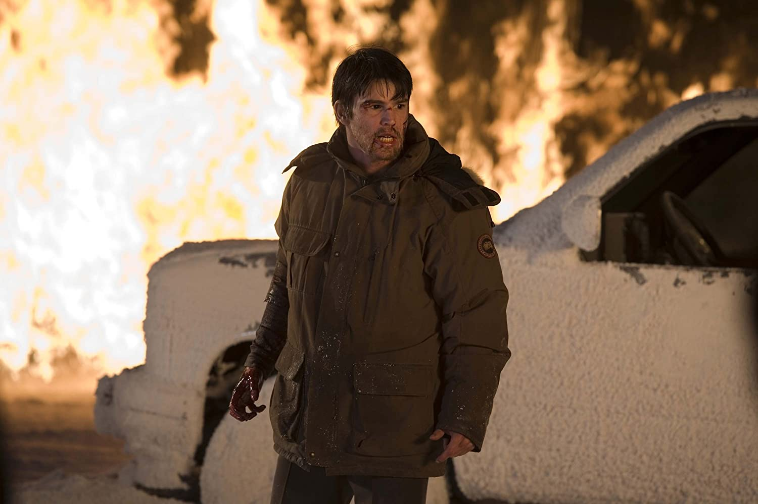 Main character Eben with fire behind him, he has black eyes from turning into a vampire