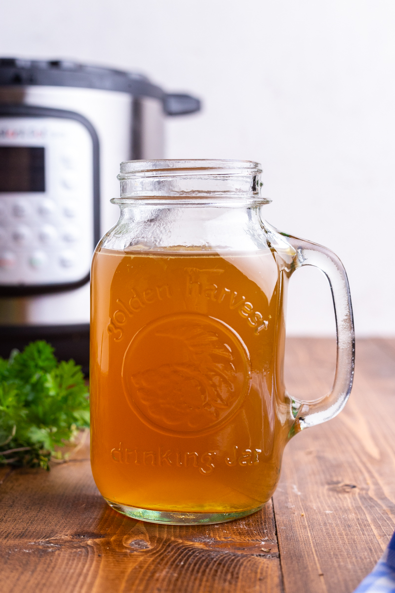 Photo of a mason jar full of homemade turkey bone broth on a wooden table with an Instant Pot in the background.