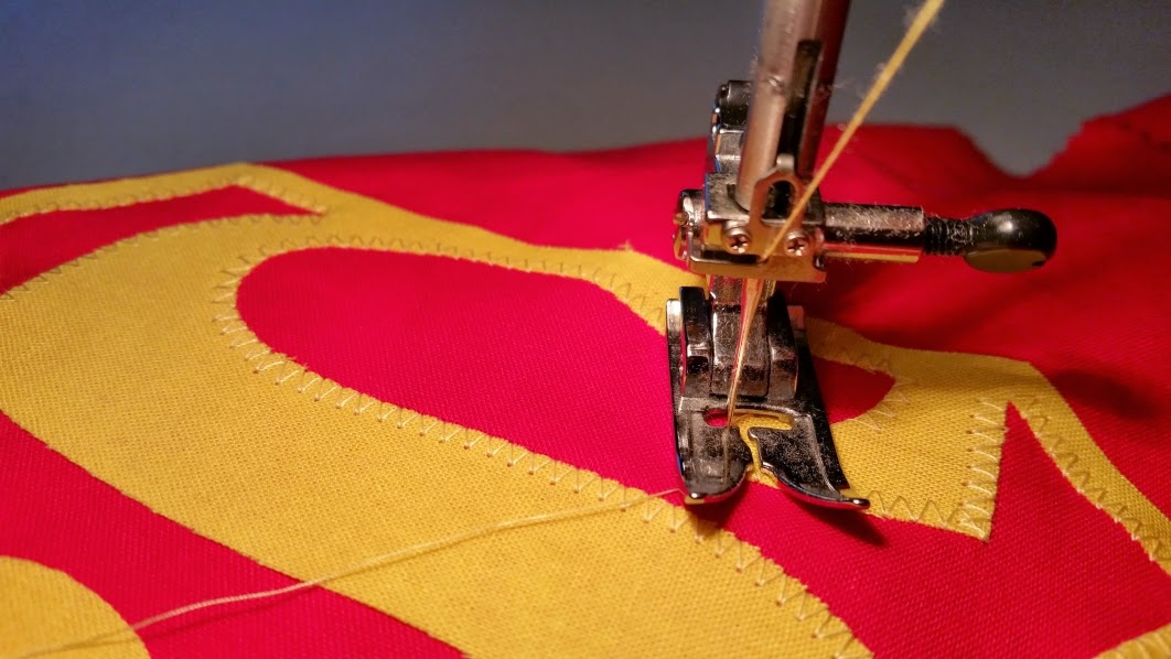 Sewing on the superhero logo patch - step 6